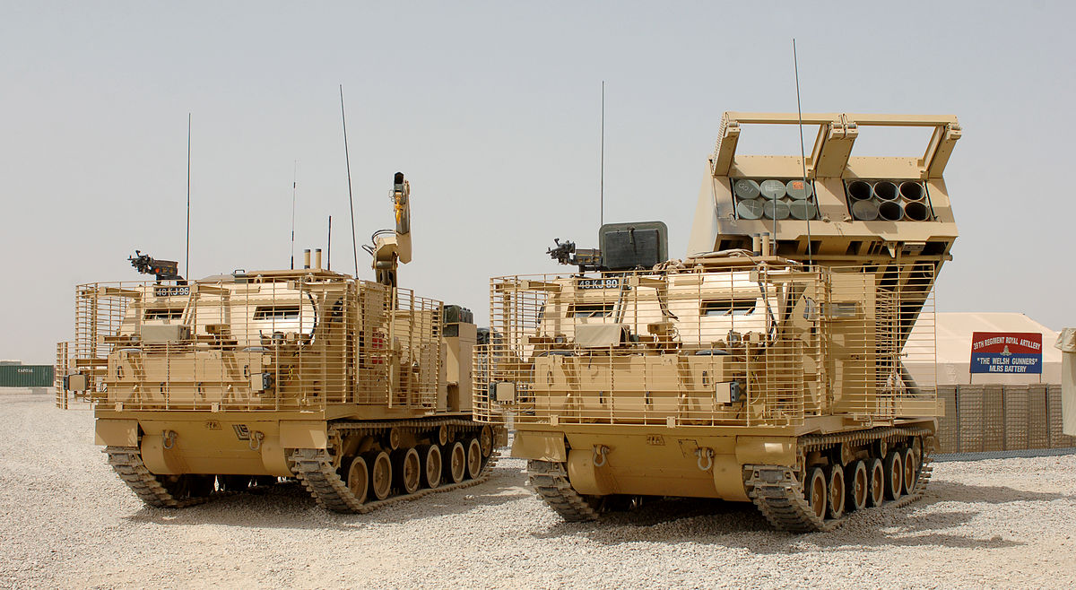 0_1483338128357_1200px-MLRS_(Multiple_Launch_Rocket_System)_Vehicles_at_Camp_Bastion,_Afghanistan_MOD_45148148.jpg